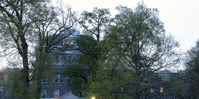 Swarthmore, USA - April 25, 2016. Evening view of Parrish Hall with a male student working on his computer on porch in the campus of Swarthmore College. Swarthmore College is a top-ranking private liberal art college in the United State. It was founded in 1864 with a total current enrollment of ~1500 undergraduate student. It is located in a garden-like suburban setting southwest of Philadelphia in Swarthmore Borough in Delaware County of Pennsylvania.