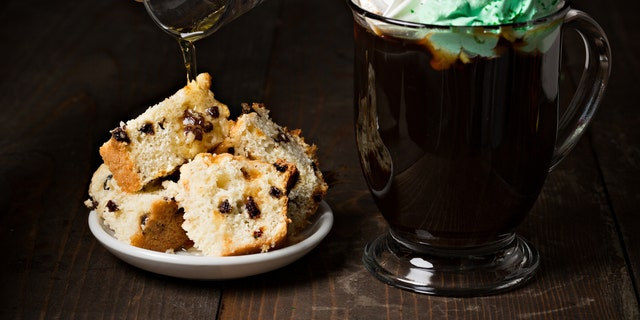 An extreme close up horizontal photograph of a hand pouring a shot of Irish whisky over some traditional Saint Patrick's Irish soda bread slices and a glass mug of Irish coffee with whipped cream and topped with green sprinkles.