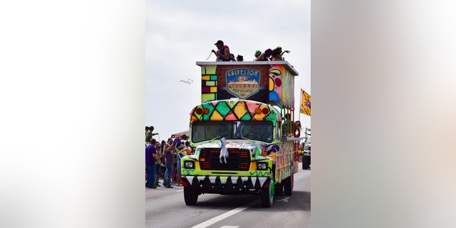 Galveston, USA - February 18, 2017:  Galveston Island Brewery celebrates by tossing necklaces from a decorated bus during the Mardi Gras parade.