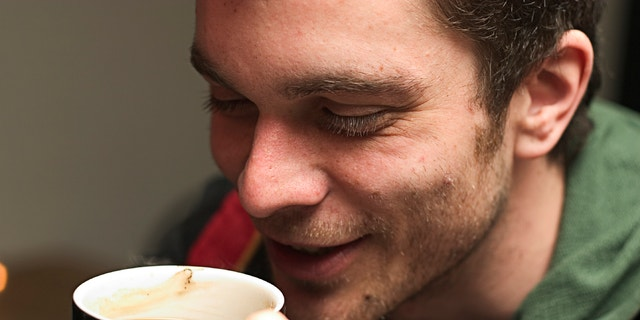 Young man enjoying a nice warm cup of coffee.