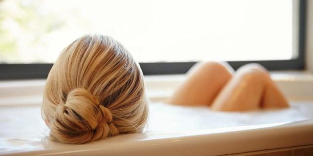 A happy young woman relaxing in a luxurious foam bath