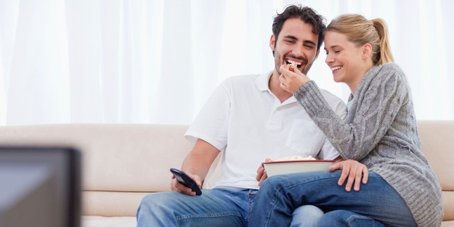 Lovely couple watching TV while eating popcorn in their living room