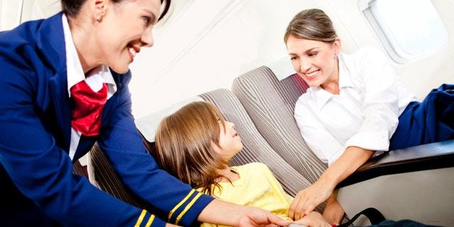Air hostess helping a kid to fasten his seatbelt
