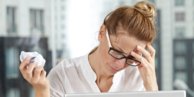A frustrated businesswoman having headache and crumpling paper