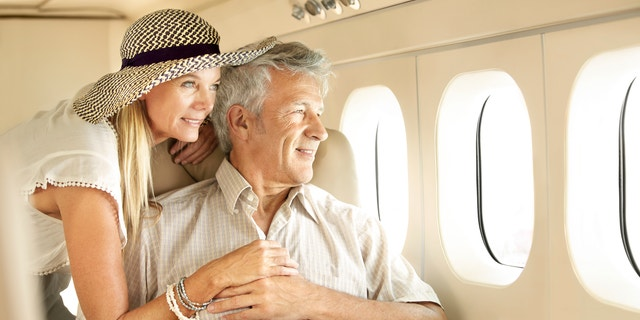 Smiling senior couple on an airplane looking out the window