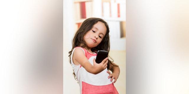 portrait of cute little happy using cell phone taking a selfie