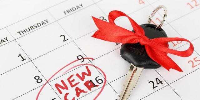car key with ribbon on calendar, new car concept