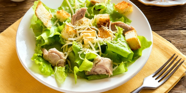 Chicken caesar salad with cheese and croutons over rustic wooden background close up