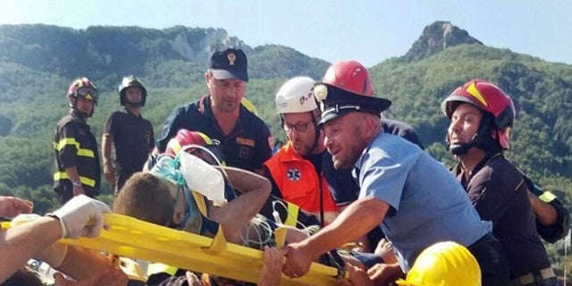 Firefighters and rescue workers pull out a boy, Mattias, from the collapsed building in Casamicciola, near Naples, Italy, a day after a 4.0-magnitude quake hit the Italian resort island.