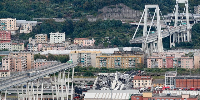 Cars are blocked on the Morandi highway bridge after a section of it collapsed, in Genoa, northern Italy, Tuesday, Aug. 14, 2018.