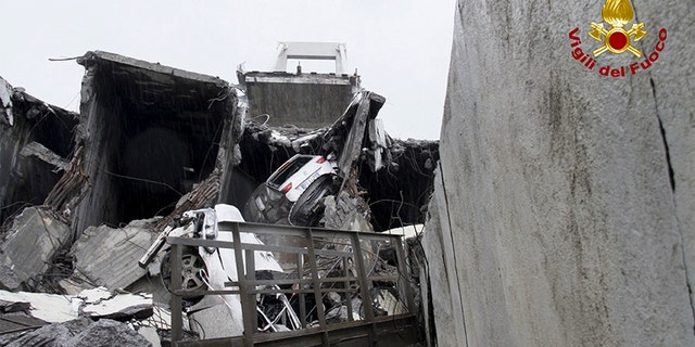 In this photo released by the Italian firefighters, cars are seen among the rubble of the collapsed Morandi highway bridge in Genoa, northern Italy on Tuesday.
