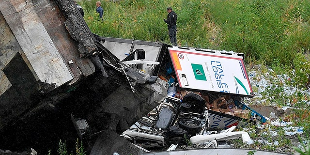 Rescuers work among the debris of the collapsed Morandi highway bridge in Genoa.