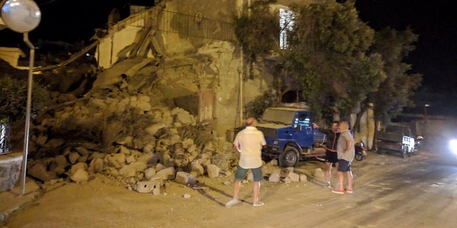 This Monday, Aug. 21, 2017 photo, shows people standing near a collapsed building following an earthquake in Casamicciola on the Italian resort island of Ischia.