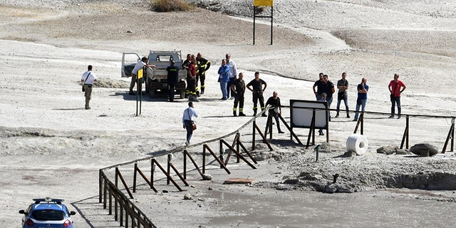 Rescuers stand on the site where three people reportedly died when they fell into a crater in a steamy volcanic field.