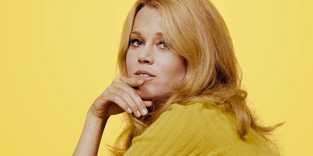 Portrait of American actress Jane Fonda, her hand on her chin, as she poses in a yellow sweater against a yellow background, 1960s.