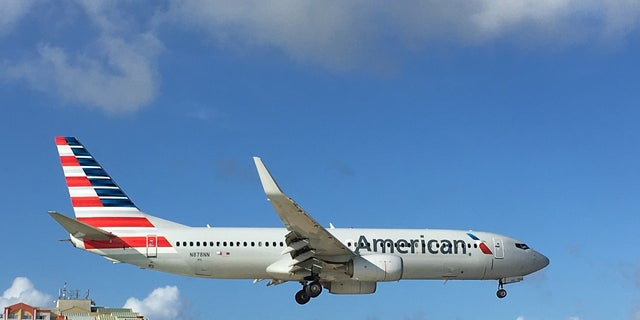 An American Airlines plane zooms over beachgoers.
