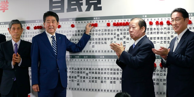 Japanese PM Shinzo Abe poses for photos as he marks on the name of one of those elected in the parliamentary lower house election in Tokyo, Sunday, Oct. 22, 2017.