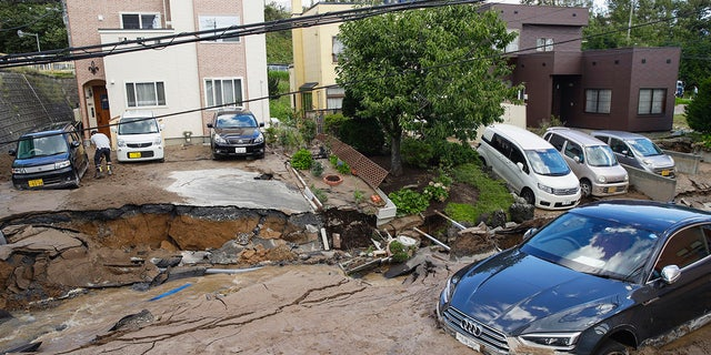 Cars are stuck in mud covered road after an earthquake in Sapporo, Hokkaido, northern Japan, Thursday.