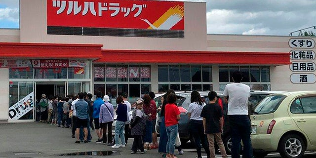 People line up outside a supermarket due to rush to buy supplies after an earthquake, in Biei town, Hokkaido, northern Japan, Thursday.