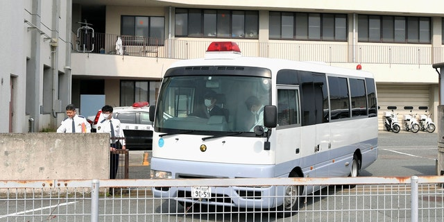 A police vehicle carrying Yoshitane Yamasaki leaves Sanda Police Station on Monday.