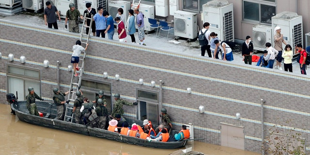 People who are stranded at a flooded hospital are rescued following heavy rain in Kurashiki city, Okayama prefecture, southwestern Japan, Sunday, July 8, 2018.