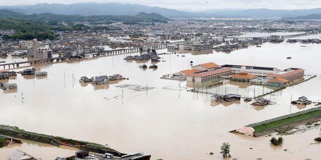 A broken embankment is seen in front in flooded Kurashiki city, Okayama prefecture, southwestern Japan, following heavy rain, Sunday, July 8, 2018
