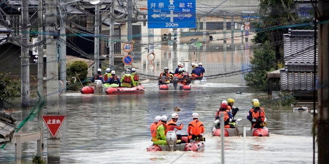 Rescuers on boats head for search in the partly submerged area in water after heavy rain in Kurashiki city, Okayama prefecture, southwestern Japan, Sunday, July 8, 2018.