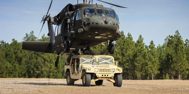 Paratroopers finish connecting a Humvee to a UH-60 Black Hawk helicopter during slingload training on Fort Bragg, N.C., Jan. 20, 2016. (Army photo by Sgt. Chad Haling)