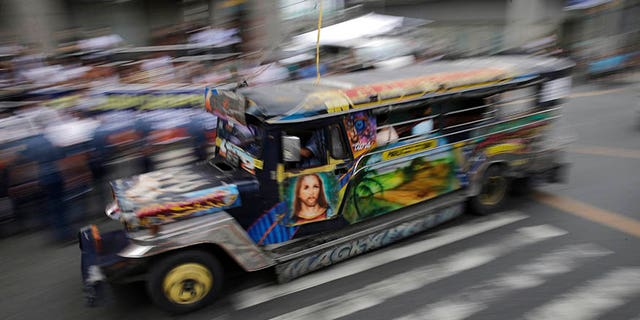 In this Oct. 16, 2017, photo, a passenger jeepney with a painting of Jesus Christ travels along a road in Manila, Philippines. The iconic passenger jeepney is chugging toward change and uncertainty as a government modernization program aims to improve their engines, safety and convenience in an overhaul that poor Filipino drivers and owners say they can't afford. (AP Photo/Aaron Favila)