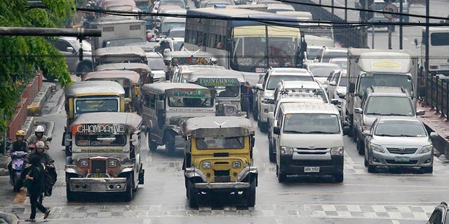 In this Oct. 6, 2017, photo, passenger jeepneys line up along Manila's streets during rush hour traffic in Manila, Philippines. The iconic passenger jeepney is chugging toward change and uncertainty as a government modernization program aims to improve their engines, safety and convenience in an overhaul that poor Filipino drivers and owners say they can't afford. (AP Photo/Aaron Favila)