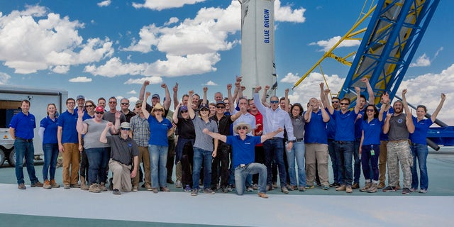 Jeff Bezos, center kneeling, takes a picture with the Blue Origin team and clients. Barnett can be seen pumping his fist above Bezos' left shoulder.