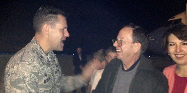 Jeffrey Fowle, (center), and his wife Tatyana were greeted by Air Force Col. John Devillier upon Fowle's arrival on American soil, on Oct. 22, 2014.