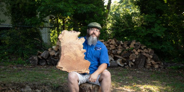 """Jeff Thornton was fined $1,000 and threatened with an arrest warrant because he had a """"disorganized"""" pile of wood in his backyard."""