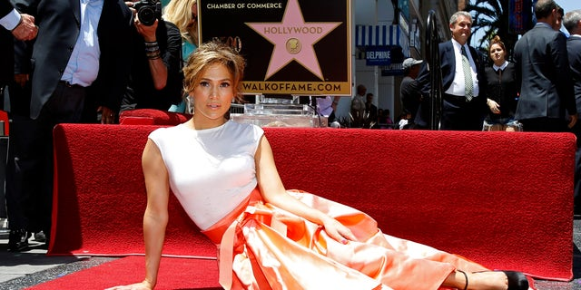 June 20, 2013. Singer and actress Jennifer Lopez poses on her star after it was unveiled on the Walk of Fame in Hollywood, California.