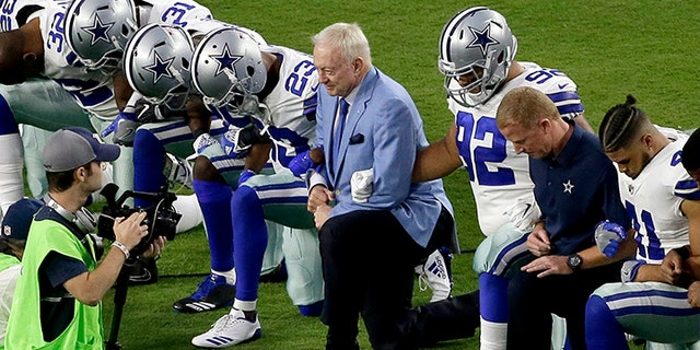 Dallas Cowboys owner Jerry Jones kneels with his players before an NFL game last season.