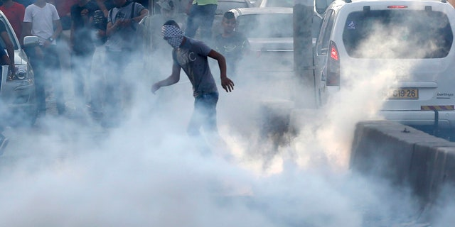 A Palestinian protester stands in tear gas during clashes near the Qalandia checkpoint between Jerusalem and the West Bank city of Ramallah, Sunday, July 23, 2017.