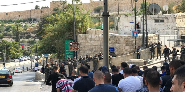 Call to prayer outside Lion's Gate entrance to Old City. Those not allowed in gather on one side of the street, police on the other.