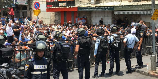 Muslim worshippers gather for Friday prayers outside the Damascus Gate entrance to Jerusalem's Old City. Israeli riot police are standing guard.
