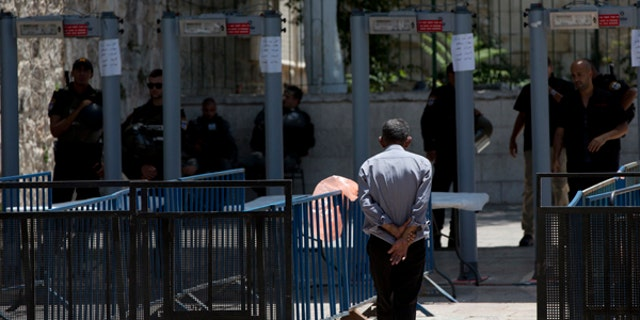 A Palestinian man walks towards a metal detector at the Al Aqsa Mosque compound in Jerusalem's Old City.