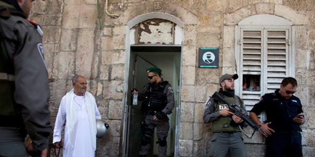 Israeli border police officers stand guard as Palestinians gather for prayer at the Lion's Gate, following an appeal from clerics for Muslims to pray in the streets instead of the Al-Aqsa Mosque compound.