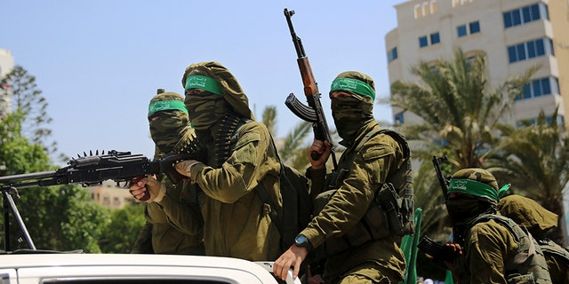 Masked militants from the Izzedine al-Qassam Brigades, a military wing of Hamas, ride vehicles during a protest against metal detectors Israel erected at the Al Aqsa Mosque compound in Jerusalem Friday.
