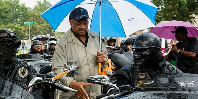 """Civil rights leader Jesse Jackson (C) greets members of the """"Outcast"""" motorcycle club before a vigil in the neighborhood where teenager Michael Brown was shot, in Ferguson, Missouri, August 16, 2014. Tensions had temporarily cooled on Thursday night but by Friday evening, protesters were again swarming through a residential and retail district in the small town outside St. Louis that has become the site of repeated clashes between protestors and police forces. The unrest erupted after Ferguson police officer Darren Wilson, 28, shot and killed Brown shortly after noon last Saturday as Brown and a friend walked down a street that runs through an apartment complex where Brown's grandmother lives. REUTERS/Lucas Jackson (UNITED STATES - Tags: CIVIL UNREST CRIME LAW TPX IMAGES OF THE DAY) - RTR42O0M"""