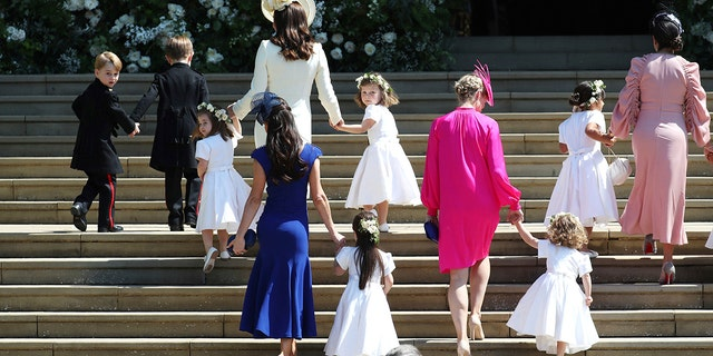 Britain's Prince George, left, Princess Charlotte, third left, Kate, the Duchess of Cambridge, background fourth left and Jessica Mulroney foreground arrive with the bridesmaids and page boys for the wedding ceremony of Prince Harry and Meghan Markle at St. George's Chapel in Windsor Castle in Windsor