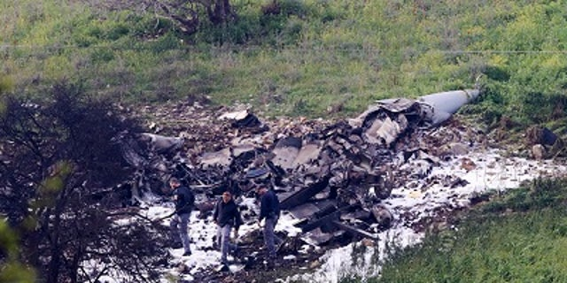 Investigators inspect the wreckage of an F-16 that crashed in northern Israel.