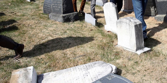 Volunteers from the Ahmadiyya Muslim Community survey damaged headstones at Mount Carmel Cemetery on Monday, Feb. 27, 2017, in Philadelphia. More than 100 headstones have been vandalized at the Jewish cemetery in Philadelphia, damage discovered less than a week after similar vandalism in Missouri, authorities said. (AP Photo/Jacqueline Larma)