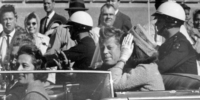 John F. Kennedy waves from his car during the motorcade in Dallas before he was shot and killed.
