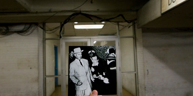 This photo from September 10, 2013 shows a picture made by Bob Jackson of the Dallas Tim Herald on November 24, 1963 by Lee Harvey Oswald, assassin of US President John F. Kennedy, as the Dallas Nightclub owner Jack Ruby in the foreground up close in a corridor of the Dallas Police Headquarters shoots him with the current scene at Dallas Police Headquarters in Dallas. (Associated Press)