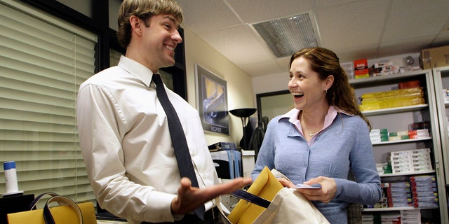 """Actors John Krasinski (L) and Jenna Fischer interact as they receive gift bags from the Screen Actors Guild Awards Committee including a certificate for their nomination for an outstanding performance by an ensemble in a comedy series in """"The Office,"""" on the set of the television show """"The Office,"""" in Panorama City, California, January 11, 2007."""