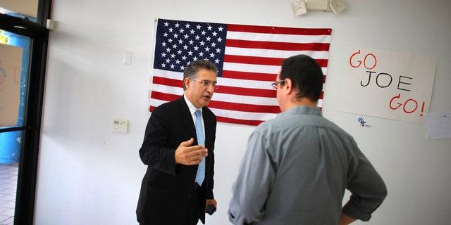 Joe Garcia (L) talks with his campaign manager, John Estes. He defeated opponent Rep. David Rivera (R-FL) in Miami, Florida.