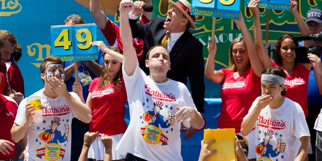 July 4, 2013: Joey Chestnut, center, wins the Nathan's Famous Fourth of July International Hot Dog Eating contest with a total of 69 hot dogs and buns, alongside Tim Janus, left, and Matt Stonie, right, at Coney Island, in the Brooklyn borough of New York.